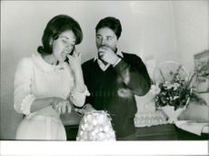 Sacha Distel with his wife, enjoying food. Photo taken Jan 30, 1963