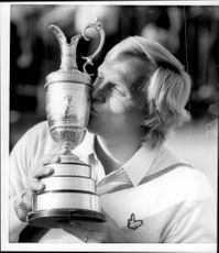 Golf player Greg Norman kisses the trophy after winning the British Open 1986