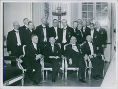 Men sitting and standing together for group photograph.