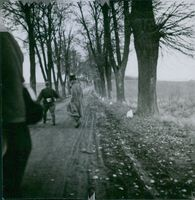 Soldiers walking on the road in the village. 1947
