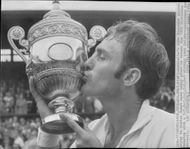 Tennis player John Newcombe kisses his cup at Center Court after winning the Wimbledon Championship