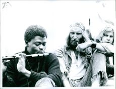 A photo of man blowing flute with are men , the other man is taking cigarette and the other one is looking towards the camera.