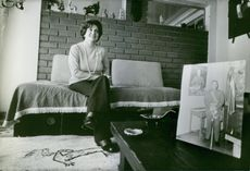 Lucía Hiriart sitting on the couch with a portrait of her husband Augusto Pinochet on the foreground.
