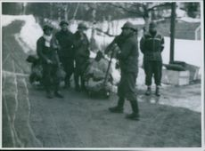 British soldiers standing in Norway, holding gun and luggage.