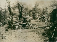 Soldiers standing in the village, beside their weapons.
