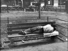 A homeless man lying on a park bench