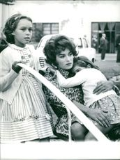 Silvana Mangano during an interval, relaxing with her two daughters Raffaella and Veronica.