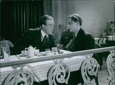 Two men sitting talking to each other. A scene in the film Night in The Port in 1943.