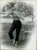A woman eating from a dish on the field.
