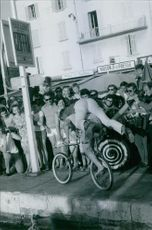 1968 A photo of  as Gilette is a former French World Cup alpine ski racer Jean-Claude Killy doing cycling with another man, people looking at him.