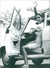 A woman in the car, smiling and waving goodbye.