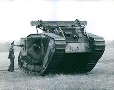 View of a huge military tank in a ground, soldier standing beside it, 1967.