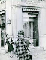 Marie-Hélène Arnaud smiling for the photographer while taking a stroll o the street.