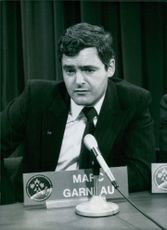 Marc Garneau sitting in front of a mike.
