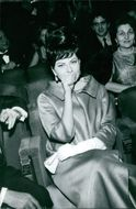 Princess Soraya of Iran  sitting, striking a pose, covering her mouth with her hand, February 1965.