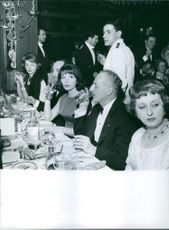 Darryl Francis Zanuck drinking water, sitting with other people.
