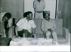 1964 A photo of men siting and talking in a room at the center is a table where in 5 glasses are there ready to use for drinking something.