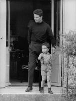Jacques Charrier standing with a child.