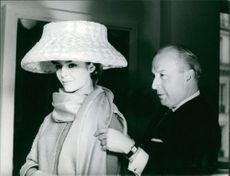 Sylvia Casablancas, in large hat, with a man.