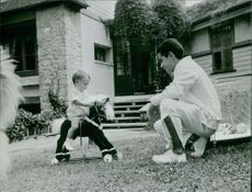 Yves Saint-Martin with a toddler riding a mini wooden horse.