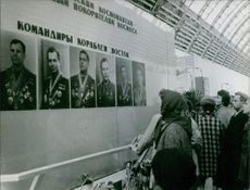 People standing and looking the photographer of general and commanders on the wall. 1965