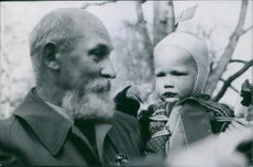 Peace celebrated in Stockholm 1945 Man lifted up a cute little baby in his arms and looking at him.