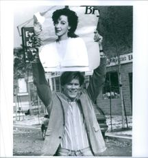 """A photo of Kevin Bacon holding a picture of Elizabeth Perkins in the 1991 in a  film, """"He Said, She Said"""". 1991"""