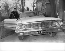 Harry Rogers standing by ford car.