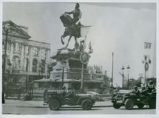 Military vehicles passing by St. Joan of Arc sculpture.