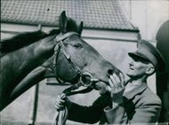 Man looking and holding snaffle of horse.