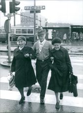 An old man crossing the road with two old women and holding hands.