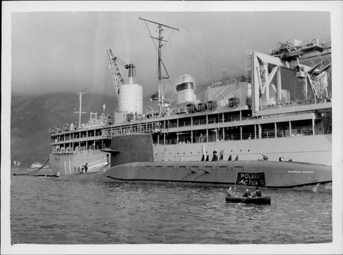 """A protector in a little eka next to the submarine Polaris """"Patrick Henry"""" in front of the ship """"Proteus"""" in Holy Loch"""