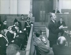 "Man speaking in courtroom in between people.   ""Bauer proceeding""  1961"