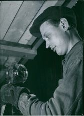 Man looking at glass material. 1950
