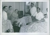People relaxing in a room and smiling while looking at the camera.