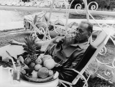 Henri Charrière relaxing and smoking beside the pool.