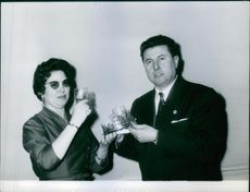 Pierre Poujade holding a crown and a glass beside a woman.