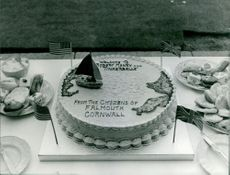 """A welcome cake for Robert Manry and his ship boat """"Tinkerbelle"""" from the citizens of Falmouth Cornwall.  Takne - Aug. 1965"""