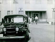 People entering in the building and a jeep standing outside.