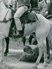 People riding horse, a man kneeling with his luggage.