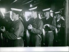 Sailors standing and holding handles.