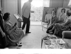 Juan Carlos I with paintings and talking to his friends.