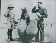 British soldiers drinking a reserved water from a jar in Africa.