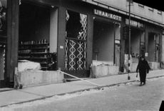 A woman is walking past a shop that's been damaged because of war. 1939-1940