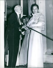 Charlie de Beistegui seen holding his cane while talking to a woman at a party. 1970.