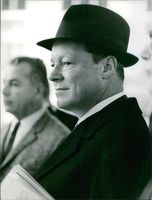 A vintage photo of Willy Brandt holding some paperwork, wearing a Tuxedo and black homburg.