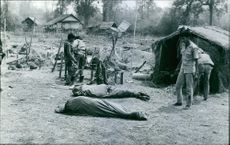 Two dead bodies lying on ground, soldiers standing there looking at it.