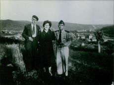 Woman standing with two men in open field. 1964