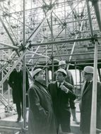 Pierre Mendès France having a conversation with another man while inspecting a building being built.