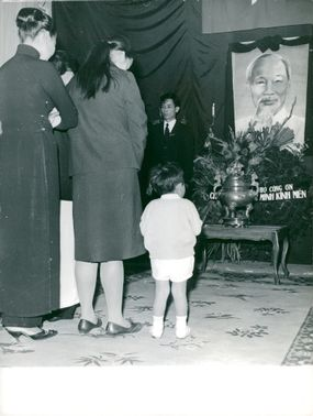 Some Vietnamese people admire a portrait of Ho Chi Minh at a ceremony in Paris